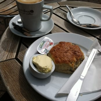 Scone with jam and clotted cream and a latte