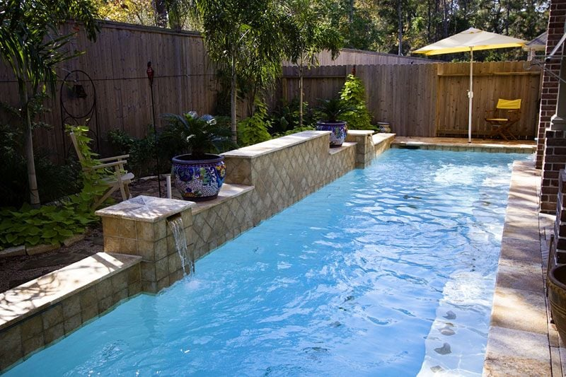 Narrow lap pool with swim jets and raised wall with for Raised swimming pool designs