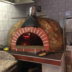 Die Pizzen werden in einem Holzsteinofen…