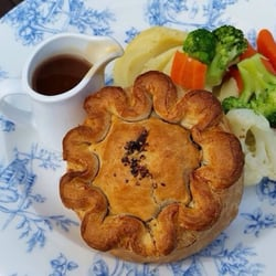 Steak and Ale Pie with Mashed Potatoes, Gravy and vegetables.