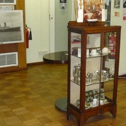 Exhibition cabinet with White Star Line silver ware and a Table from the White Star Line Ship RMS Majestic sitting just behind.