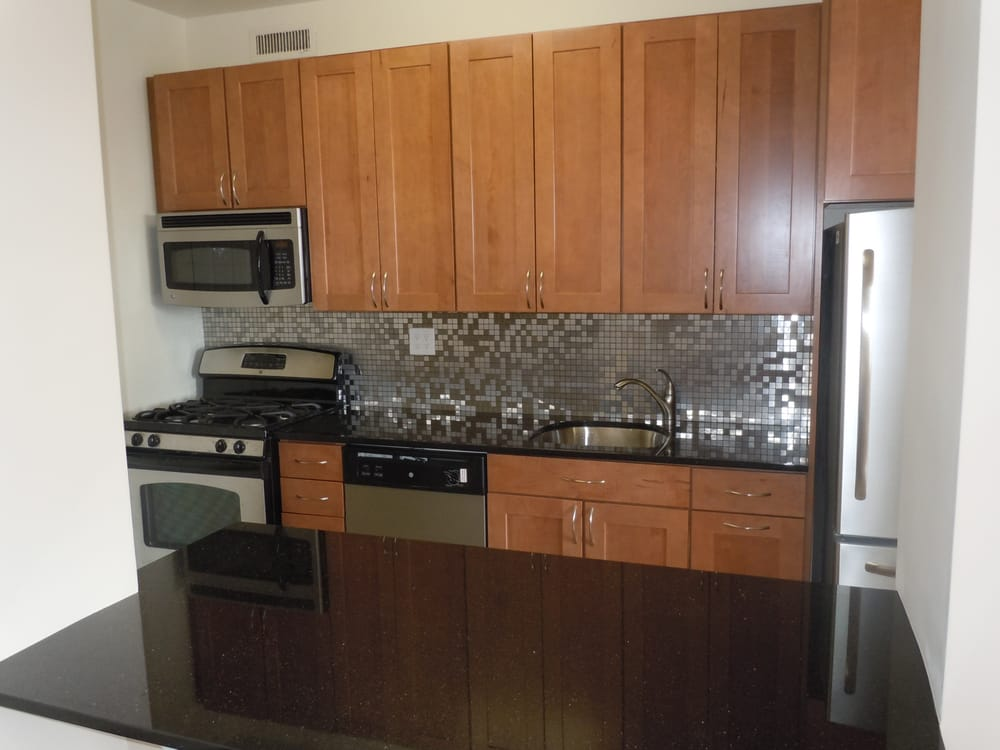 kraftmaid walnut cabinets stainless backsplash black