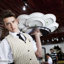 Young waiter at Tordilho Negro carrying about 40 empty dishes!