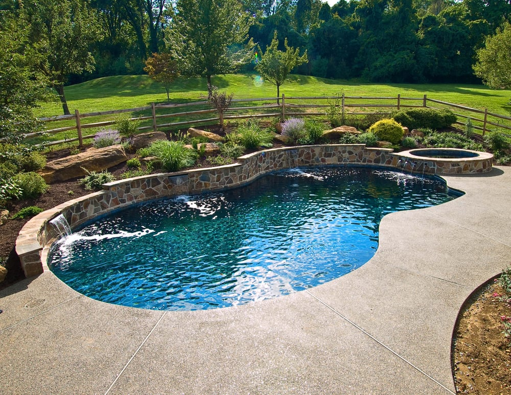 Beautiful raised stone wall with three water descents for Raised swimming pool designs