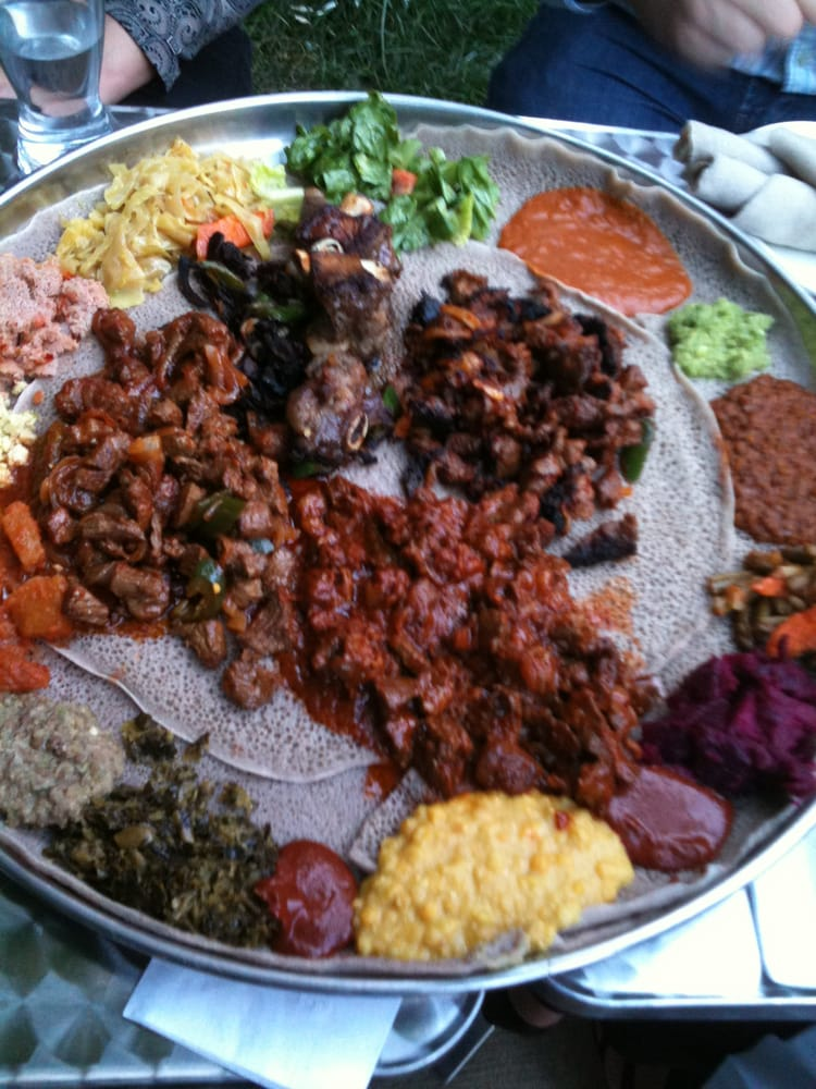 Several meat dishes and veggie sampler around the outside for Abol ethiopian cuisine silver spring md