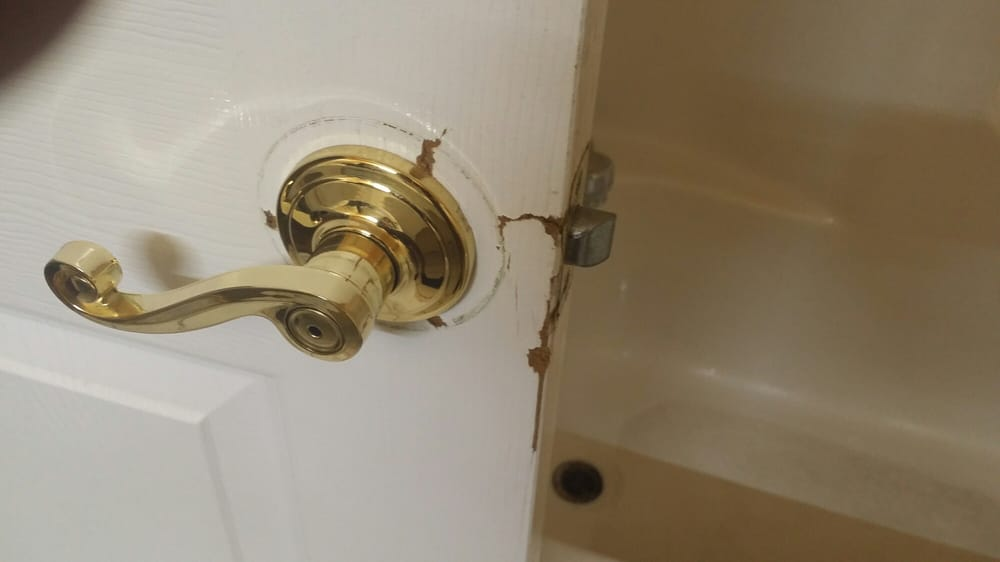 Broken bathroom door and rusted brown tub drain in background (zoom ...