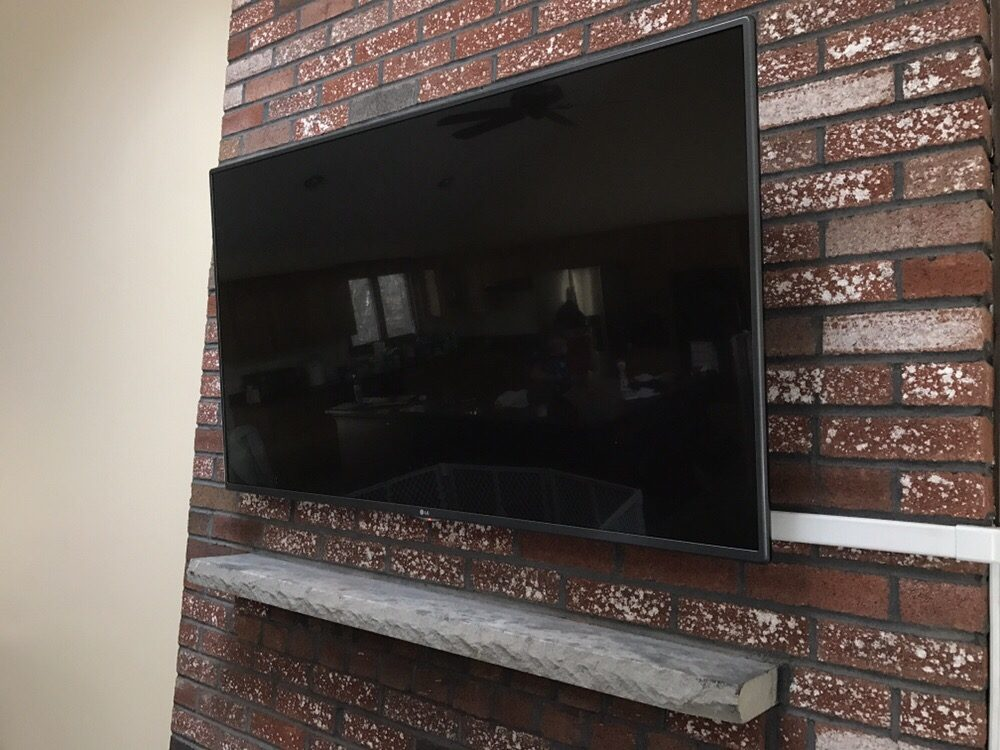 55 TV Mounted Above Brick Fireplace W Wire Mold To