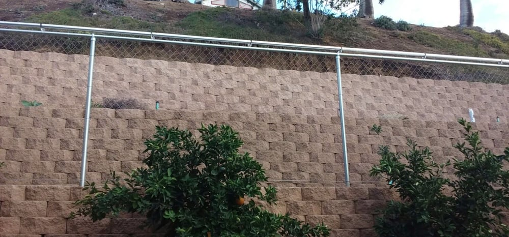 Chain Link Fence Mounted On Top Of Block Wall It Has