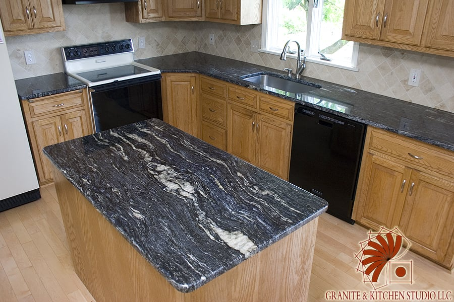 Cosmic Black Granite Countertops with a Crema Marfil Tile ... on Black Granite Countertops With Backsplash  id=33326