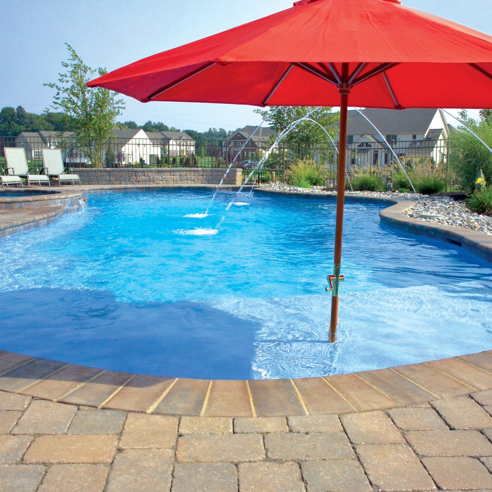 Free-form concrete pool with brick coping, laminar deck jets ...