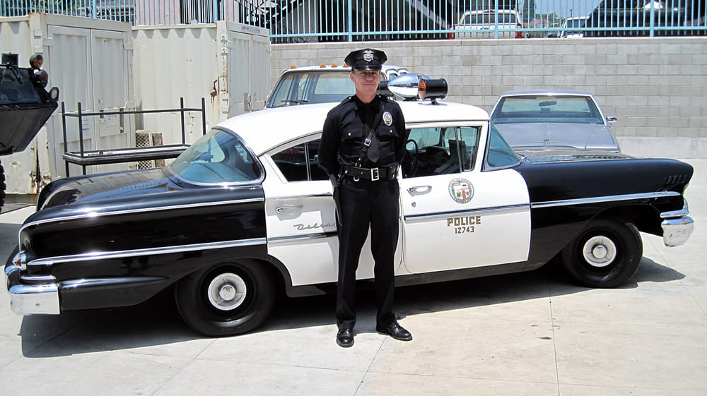 Car Museum Los Angeles >> Volunteer Police reenactor standing at parade rest next to a restored 1958 Chevrolet Delray LAPD ...