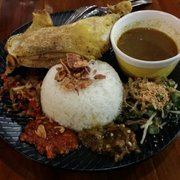 Fried barramundi fillet with Makassar sauce Photo of Naughty Nuri's -  Melbourne Victoria, Australia. Balinese chicken on coconut rice