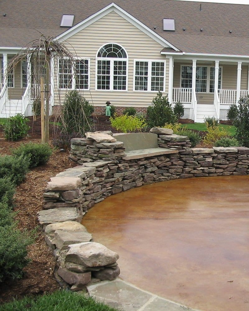 A Natural Stone Wall And Stained Concrete Patio Combine