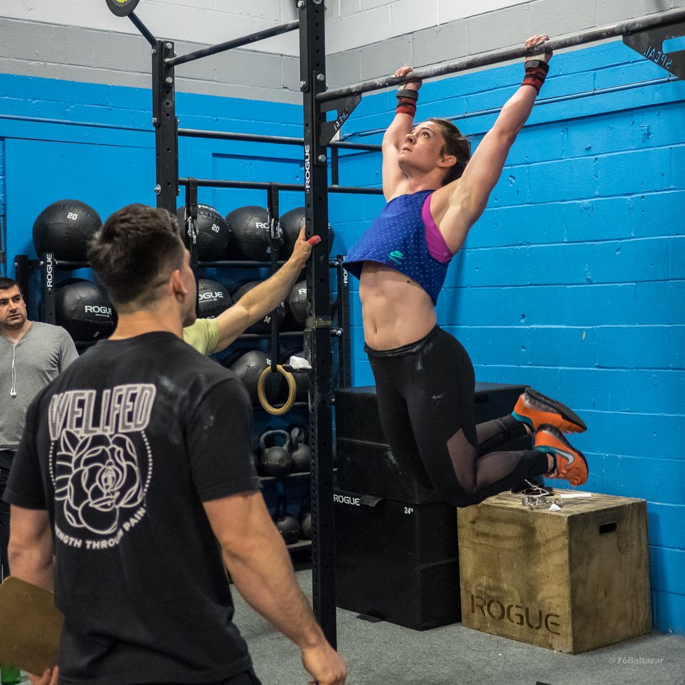 Photo of CrossFit Queens - Astoria, NY, United States. a member does a pull up during Open Workout 17.3, while her coach supervises