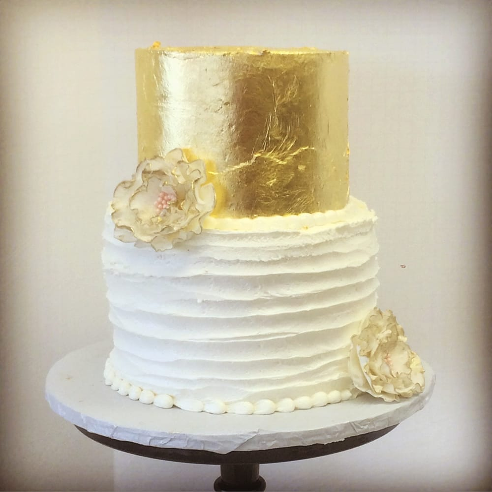 Two tiered buttercream and gold leaf wedding cake with ruffled sugar ...