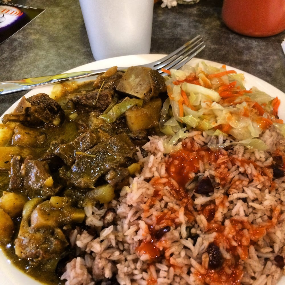 curry goat with beans and rice and vegetables really good