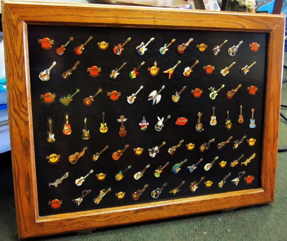 Shadow box frame holds a large collection of Hard Rock Cafe pins ...