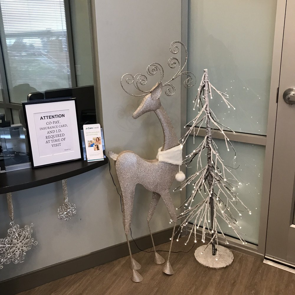 Christmas tree and slim ring deer at the check in area - Yelp