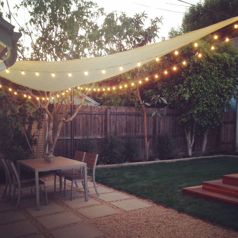 Backyard with pavers and shade sail with string lights | Yelp on Shade Sail Backyard Ideas id=59783