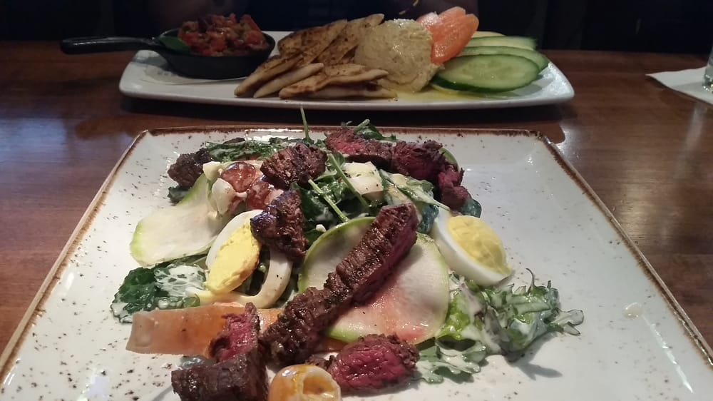 Grilled hanger steak salad and hummus in the background ...