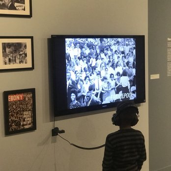 Photo of California African American Museum - Los Angeles, CA, United States. Young African American boy listening to Dr. MLK's speeches on Equality.