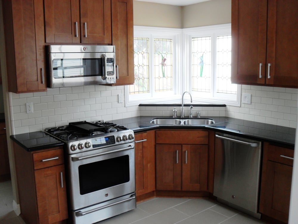 Brentwood sandalwood shaker cabinets absolute black for Black kitchen cabinets white subway tile