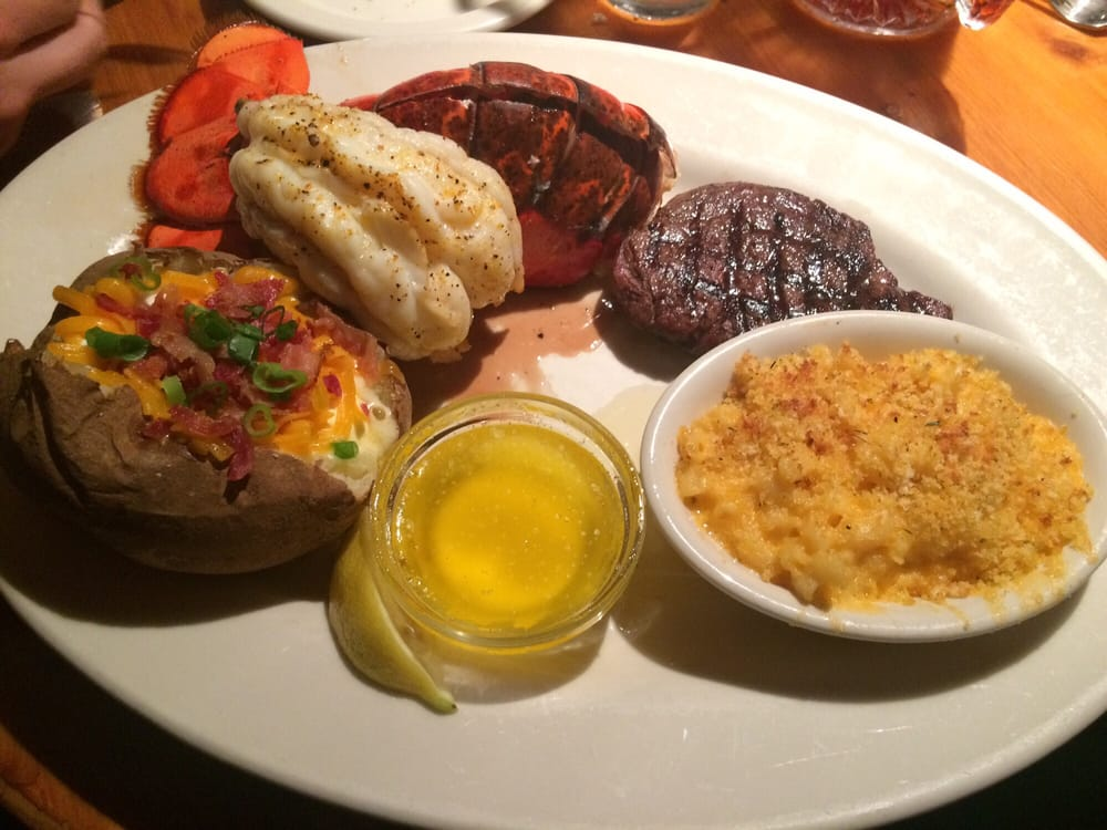 Youuuumm! Filet Mignon with large lobster tail, Mac and cheese, and a fully loaded baked potato ...