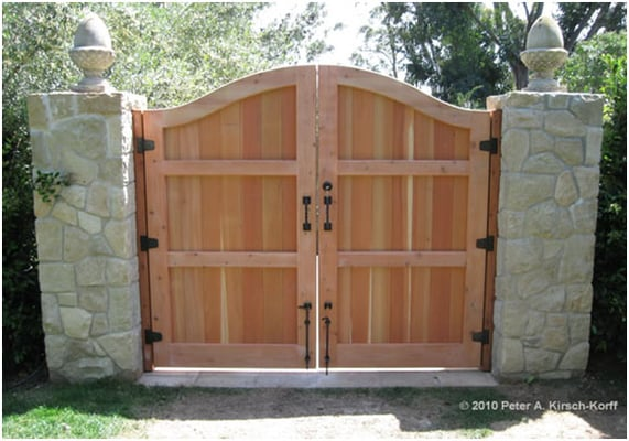 A Solid Yet Elegant Wood Driveway Gate With Stone Pillars